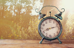 Image of vintage alarm clock on wooden table in front of rustic country side landscape background. retro filtered Stock Image