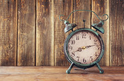 Image of vintage alarm clock on wooden table in front of wooden background. retro filtered.  stock image