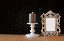 Image of vintage antique classical frame and Burning candle on wooden table and black textured background Royalty Free Stock Photo