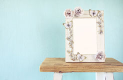 Image of vintage antique classical frame on wooden table. Vintage filtered Stock Image
