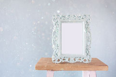 Image of vintage antique classical frame. On wooden table. vintage filtered with glitter overlay Royalty Free Stock Photography