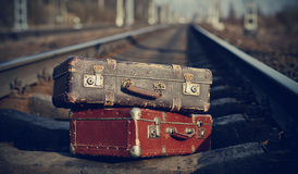 The image of vintage suitcases forgotten on railway tracks. Royalty Free Stock Image