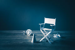Image with vintage texture of a Director chair and movie items. High contrast vintage image of Director chair and several movie items made from paper on a wood stock photo