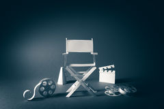 Image with vintage texture of a Director chair and movie items. High contrast vintage image of Director chair and several movie items made from paper on a wood royalty free stock image