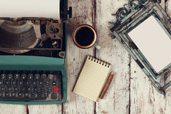 Image of vintage typewriter and blank frame on wooden table Stock Photos