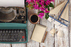 Image of vintage typewriter, blank notebook, cup of coffee and old sailboat on wooden table Stock Image