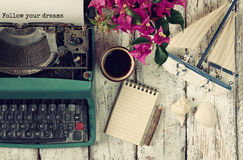 Image of vintage typewriter with phrase Follow your dreams, blank notebook, cup of coffee and old sailboat. On wooden table Royalty Free Stock Photos