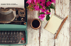 Image of vintage typewriter with phrase. Share your story, blank notebook, cup of coffee on wooden table Stock Image
