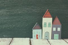 Image of vintage wooden colorful houses decoration on wooden table  in front of  blackboard. faded retro filtered image Royalty Free Stock Image
