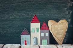 Image of vintage wooden colorful houses and fabric heart on wooden table in front of blackboard Royalty Free Stock Photo