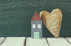 Image of vintage wooden colorful houses and fabric heart on wooden table in front of blackboard. faded retro filtered image Stock Photography