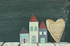 Image of vintage wooden colorful houses and fabric heart on wooden table in front of blackboard. faded retro filtered image Stock Photo