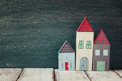 Image of vintage wooden colorful houses on wooden table in front of blackboard. Image of vintage wooden colorful houses on wooden table in front of blackboard Stock Photography