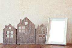 Image of vintage wooden house decor, blank frame on wooden table and stars garland. selective focus.  Stock Photos