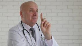 Image Warning医生与手势的微笑和指向与手指的 库存照片