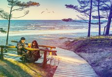 Happy elderly couple with a pet resting on wooden bench Stock Image