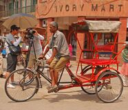 An elderly model, photographer and helper are working together to get the perfect shot of trishaw rider on the job