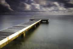 Wooden pier at sunset taken with a long exposure stock photos