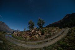 This image was taken using fisheye lens. The night sky is blue and there are many stars in the sky. There is a gravel road in the royalty free stock image
