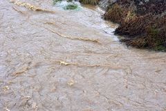 Image of water stream flood with strong current, Sarajevo, Europe, 03.02.2018. Image of water stream flood with strong current. City stream during rainy season royalty free stock photography