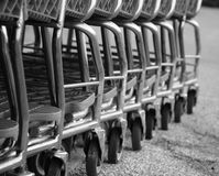 Image of wheels of row of parked shopping carts equipped with coin-operated locking mechanisms. Black and white image of wheels of row of parked shopping carts Stock Photography