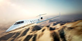 Image of white modern and luxury generic design private jet flying in blue sky at sunset.Uninhabited desert mountains Stock Image