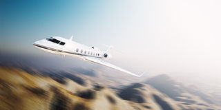 Image of white modern and luxury generic design private jet flying at sunrise over uninhabited desert.Mountains Stock Images