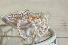 Image of white pearls necklace and diamond tiara on vintage table. vintage filtered. selective focus Royalty Free Stock Photos