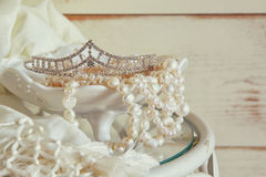 Image of white pearls necklace and diamond tiara on vintage table. vintage filtered. selective focus Stock Images