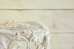 Image of white pearls necklace and diamond tiara on vintage table. vintage filtered. selective focus.  Stock Images