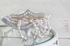 Image of white pearls necklace and diamond tiara on vintage table. vintage filtered. selective focus Stock Photos