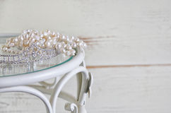 Image of white pearls necklace and diamond tiara on vintage table. vintage filtered. selective focus.  Royalty Free Stock Images