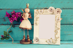 Image of white vintage blank frame and cute fairy princess on wooden table. Royalty Free Stock Photos