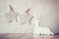 Image of white wooden reindeer and glitter stars hanging on rope over glitter silver background. retro filtered Stock Photography