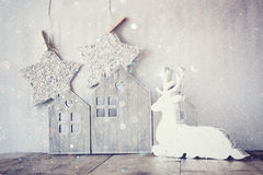Image of white wooden reindeer and glitter stars hanging on rope over glitter silver background. retro filtered Royalty Free Stock Photo