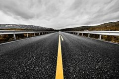 Image of a wide open prairie and mountains with a paved highway road stretching out as far as the eye can see with beautiful natur. E under a dark cloudy sky in stock photography
