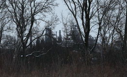 Image of winter landscape with industrial plant and dead trees Stock Image