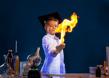 Image of witted boy holding fire in his hands. Close-up royalty free stock images