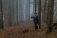 Image of a woman asking if it is the right path in the middle of the forest stock image