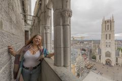 Image of a woman in the belfry of the city of Ghent Belgium and the facade of the Cathedral of St Bavon in the background. On a wonderful and cloudy day royalty free stock image