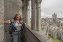 Image of a woman in the belfry of the city of Ghent Belgium. And the church of St. Nicholas in the background on a relaxed and cloudy day enjoying the city stock images