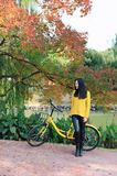Image of woman with bicycle in a park. Pretty woman with bicycle in a park at autumn Royalty Free Stock Photo