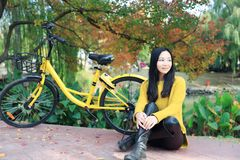 Image of woman with bicycle in a park. Pretty woman with bicycle in a park at autumn Royalty Free Stock Image