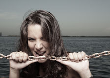 Image of a woman biting a chain Stock Image