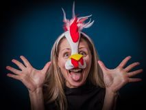 Image of a woman in chick costume with hands up. Having fun. One beautiful emotional happy blonde woman with long hair and mask as chick. Colorful studio Royalty Free Stock Images