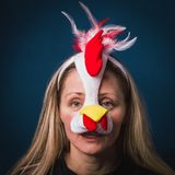 Image of a woman in chick costume with sad look. Mixed feelings. Image of a melancholywoman in chick costume with  sad facial expression, on the blue background Stock Images