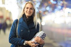 Image of woman in coat with gift in box. On background of blurred multicolored lights Stock Images
