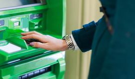 Image of woman in coat at green cash machine. In room royalty free stock photo