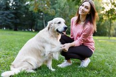 Image of woman with dog giving paw on lawn in summer park Royalty Free Stock Photo