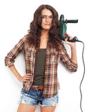 Image of woman with drill over white wall Royalty Free Stock Photos